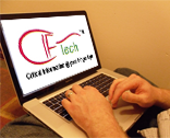 `A man using a laptop with a IT company logo